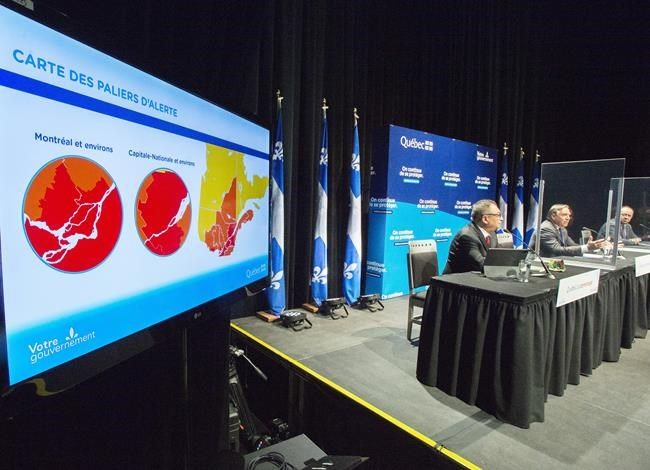 Quebec's Public Health Director Horacio Arruda, left, Quebec Premier Francois Legault and Health Minister Christian Dube, right, speak to the media at the daily COVID-19 press briefing in Montreal, Tuesday, Oct. 13, 2020. Heath authorities in Quebec are reporting 844 new cases of COVID-19 today -- in addition to 359 new cases reported during the past three days that they say were uncounted due to a technical problem. THE CANADIAN PRESS/Ryan Remiorz
