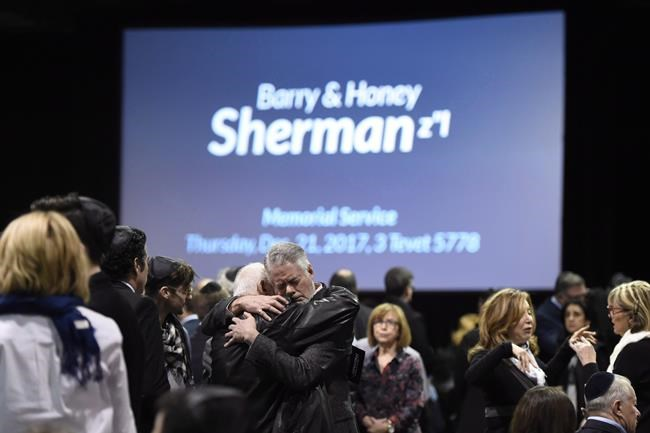People embrace before the start a memorial service for Apotex billionaire couple Barry and Honey Sherman in Mississauga, Ontario on Thursday, December 21, 2017. Toronto police say they have identified a person of interest in the high-profile 2017 homicides of a billionaire philanthropist couple. THE CANADIAN PRESS/Nathan Denette