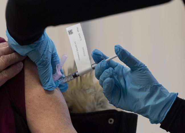 The Pfizer-BioNTech COVID-19 vaccine is administered to a personal support worker at the Ottawa Hospital Tuesday December 15, 2020 in Ottawa. THE CANADIAN PRESS/Adrian Wyld