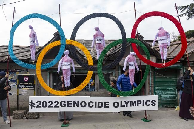 """FILE - In this Feb. 3, 2021, file photo, exile Tibetans use the Olympic Rings as a prop as they hold a street protest against the holding of the 2022 Beijing Winter Olympics, in Dharmsala, India. Groups alleging human-rights abuses in China are calling for a full boycott of the Beijing Olympics, which is sure to ratchet up pressure on the International Olympic Committee, athletes, sponsors, and sports federations. A coalition of activists representing Uyghurs, Tibetans, residents of Hong Kong and others, issued a statement Monday, May 17, 2021 calling for the """"full boycott,"""" eschewing lesser measures like """"diplomatic boycotts"""" and negotiations with the IOC or China. (AP Photo/Ashwini Bhatia, File)"""