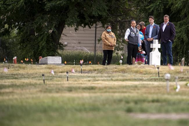 Chief Cadmus Delorme, left to right, Prime Minister Justin Trudeau, and Saskatchewan Premier Scott Moe walk though a field prior to a ceremony at the site of a former residential school where small flags which were placed, last month, in spots where ground-penetrating radar detected a potential 751 unmarked graves, in Cowessess First Nation, Sask., Tuesday, July 6, 2021. THE CANADIAN PRESS/Liam Richards