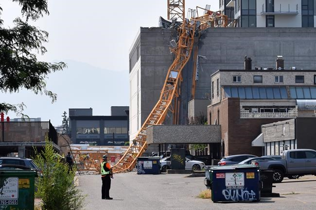 A worker looks on as a police officer investigates a collapsed crane resting on the building it damaged in Kelowna, B.C., Monday, July 12, 2021. The crane was being used on the building site of the 25-storey Brooklyn at Bernard Block residential tower, currently under construction. Once person was killed and two others were transported to hospital as a result of the collapse. THE CANADIAN PRESS/Alistair Waters