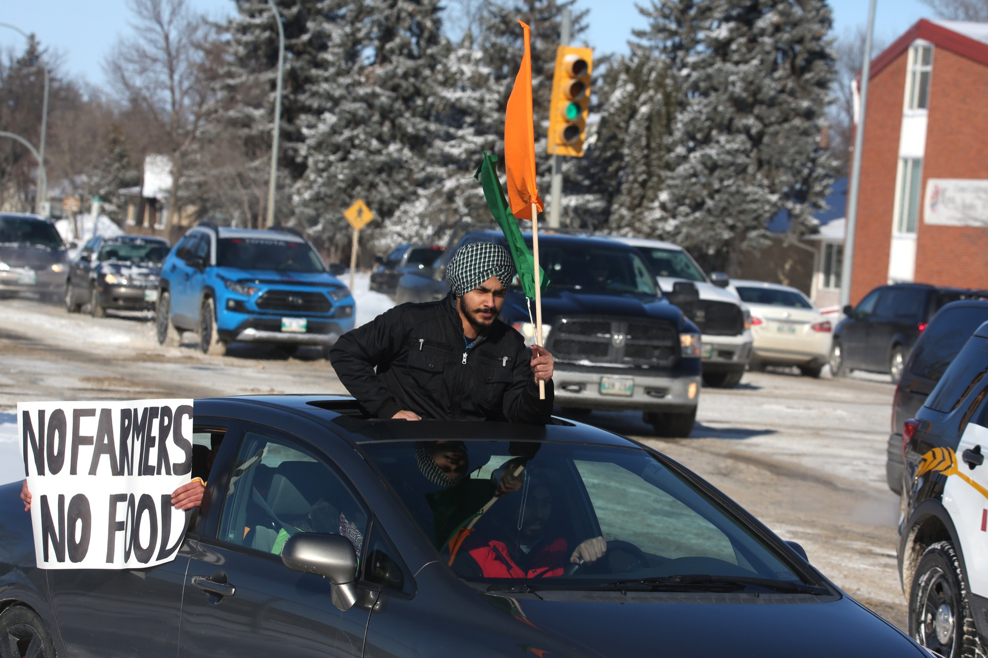 Participants of Saturday's rally in support of India's farmers hold signs and flags out of a vehicle while making their way down 18th Street in Brandon.