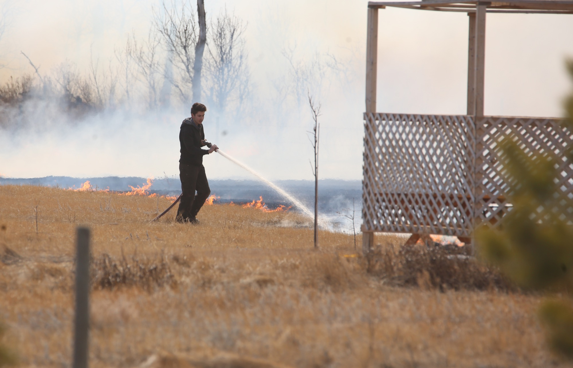A firefighter tries to put out a large grass fire near Carberry on Thursday afternoon. (Drew May/The Brandon Sun)