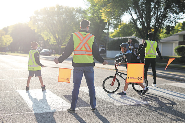 Teammates Braden Schneider and Caiden Daley help out CAA school safety patroller Brady Shields from Linden Lanes School at a crosswalk before the first day of school on Sept. 4, 2018.