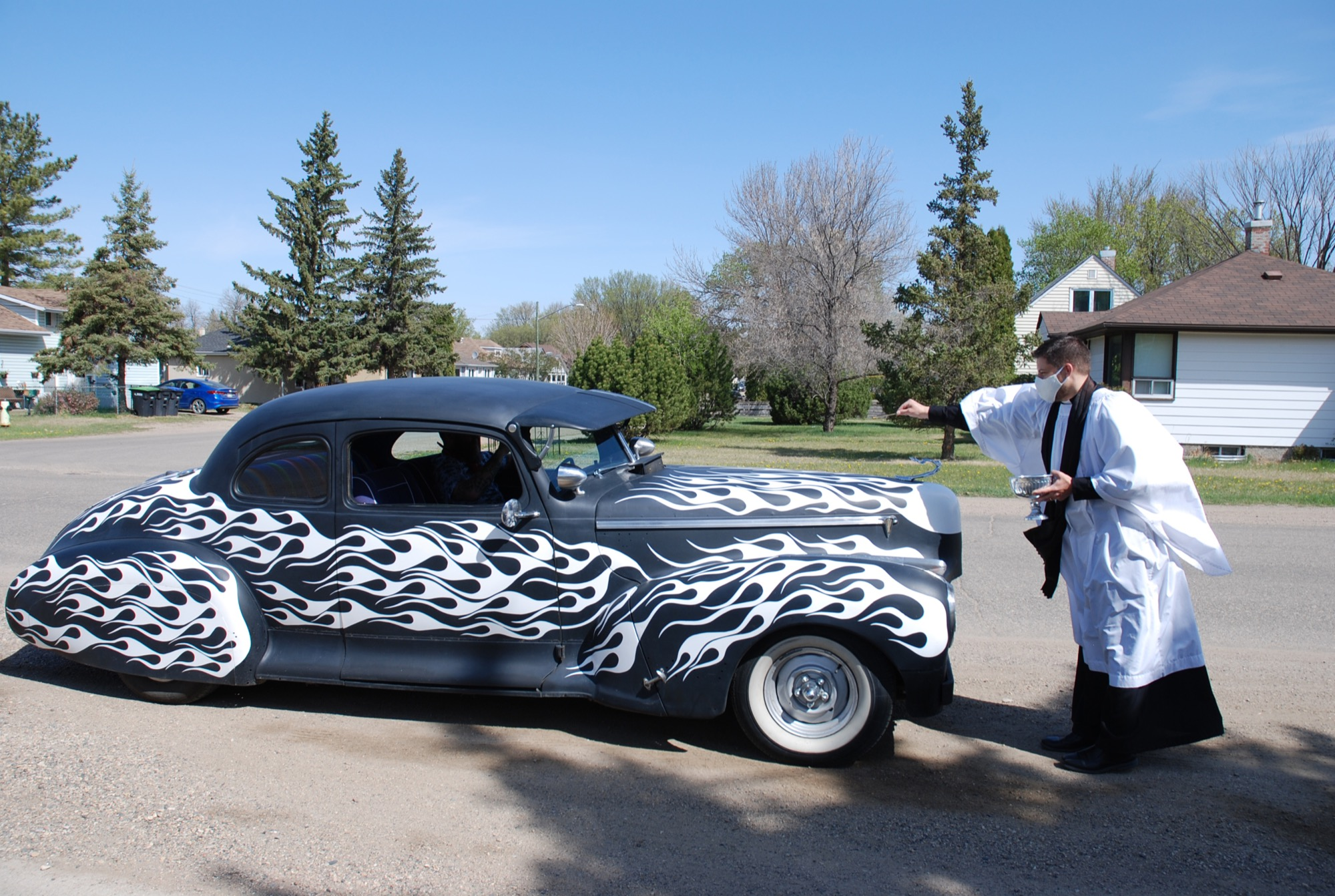 """Hoskin blesses a 1946 Hudson Coupe during """"Blessing of the Wheels"""" on Sunday while Trevor Calinwich sits in the driver's seat."""