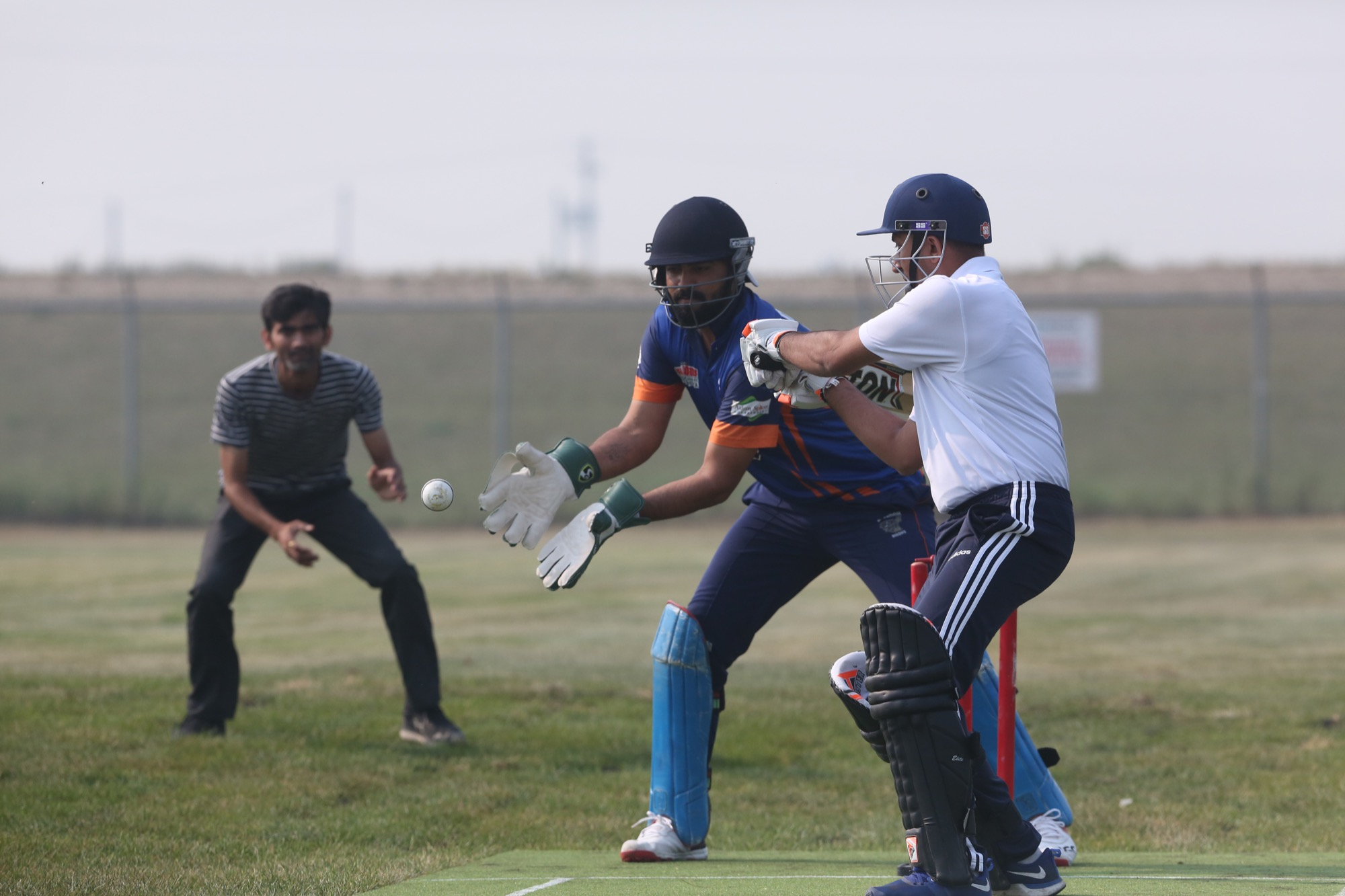 Deep Chaudhary, wicket keeper for the Vice President's 11 exhibition cricket team, reaches for the ball following a pitch and an outside bounce from the bowler on Saturday morning. The match between the President's 11 and the Vice President's 11 marked the inaugural game at the new J&G Homes Cricket Field, which was completed on July 25.