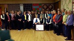 The entire quilting group poses for a photo.