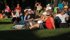 Folk fest goers sit in the glow of the evening sun as they took in Friday's music artist on the main stage at the 30th annual Brandon Folk Music and Arts Festival on the Keystone Centre grounds.