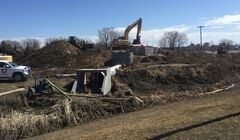 Crews work on the dike near the corner of 18th Street and Kirkcaldy Drive on Friday.