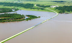 Floodwaters in the Assiniboine River Valley, northeast of Virden, reach the road level on Highway 259 on Thursday.