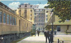 A colour postcard showing the back of the Prince Edward Hotel and a passenger train in the station.