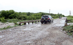A Dakota Ojibway Police Service vehicle crosses a bridge over a swollen creek to check on evacuated houses on the north side of Sioux Valley Dakota Nation northwest of Brandon on Monday.