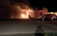 Flames engulf the rear of a mobile home early Sunday morning at the Glendale Mobile Homes Park. Police said three residents at the home escaped, but were taken to hospital for smoke inhalation.