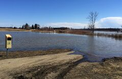 Water partially covers walking paths near the Riverbank Discovery Centre.