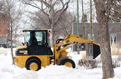 A worker in a front-end loader clears snow from the sidewalks surrounding Stanley Park on a bitterly cold Tuesday.