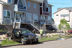 A Brandon Police Service officer investigates the scene of a serious overnight crash on Stickney Avenue in Brandon. A Ford pickup truck smashed through the railings and steps leading up to a set of Manitoba Housing units around 3:45 a.m. on Friday.