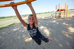 Evan Coleman, 7, spins around on a piece of play equipment at the Riverbank Discovery Centre on Tuesday.