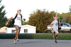 Brothers Alex and Colin Cook run across Young Street to their school bus stop on the first day of school on Wednesday morning.