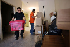 Ronald Anchiuk and Rick McClelland help Heather Sharpe move into her apartment in Massey Manor on Thursday.