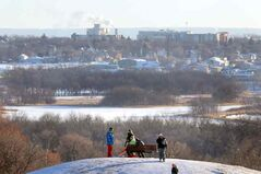 Brandon's east end is seen in the background as sledders climb Hanbury Hill on Monday afternoon. Extended hours at the sledding hill and the skating oval off 18th Street helped Brandonites have a bit of outdoor fun on New Year's Eve.