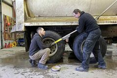 Roman Velykopolskyy and Max (no last name given) from Ukraine install new tires on  a truck at Denray Tire on Park Avenue East on Wednesday. Denray Tire is among a variety of Brandon businesses that have hired skilled workers  from other countries.