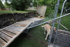 Soaked ground and wind combined to topple this retaining wall as well as the fence in the background, on Antelope Bay in Brandon on Tuesday evening. People throughout Westman continue to assess damage and clean up after the third torrential downpour in four days.