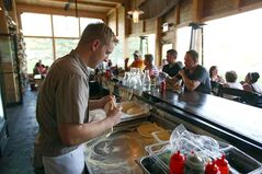 Owner Tyler Kaktins rolls out the pizza dough as the cafe buzzes with diners on a recent Saturday evening.
