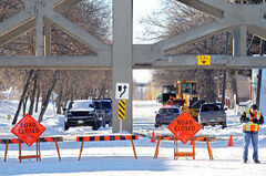 Traffic barricades block traffic along Assiniboine Avenue after a garbage truck struck a crossbeam under the Eighth Street Bridge on Tuesday.