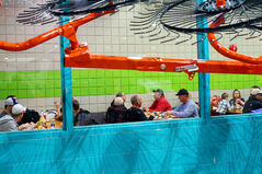 Visitors to Manitoba Ag Days enjoying lunch are framed by farm equipment.