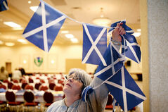 Barb Andrew, treasurer with the Westman Scottish Society, hangs Scottish flag bunting while helping prepare the Scottish Pavilion at the Victoria Inn Imperial Ballroom on Wednesday for the Lieutenant Governor's Winter Festival, which begins this evening.