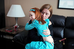 Cheryl Mauthe gets a hug from her six-year-old daughter Emily Clark in the living room of their home in Brandon on Thursday afternoon. Mauthe, who has been dealing with her seven-year-old son Colin's leukemia, was recently diagnosed with breast cancer.