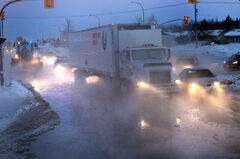 Traffic moves slowly after a water main break on Route 90 at Selkirk Avenue in Winnipeg on Tuesday.