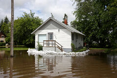 Sandbags surround a portion of a home inundated with water on King Street in Virden as the Gopher Creek continued to rise on Monday. As of late Tuesday, Virden was among 34 communities that declared states of local emergency.