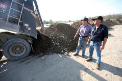 Doug Calverley (right), owner of Dougs Mobile Service in Melita, along with friend Doug Jones watch a truck unload dirt for a dike along his business' riverfront property Friday.