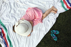 Three-year-old Eleanore Wilts sleeps on a blanket under a sun hat Saturday at the Multicultural Summer Festival.