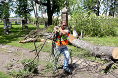James Stewart, with the city's parks and recreation department, works to clean up downed trees and branches from the Brandon Municipal Cemetery on Monday after the thunderstorm caused significant damage to the grounds, right.