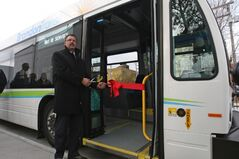 Brandon Mayor Rick Chrest prepares to cut the ribbon on the new downtown Brandon bus terminal at Eighth Street and Rosser Avenue Thursday. The ribbon was placed in the door of one of four new city transit buses that began operation earlier this year.