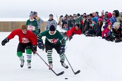 Spectators watch the action as the area residents take on the Parks Canada staff in the Canada 150 Heritage Hockey Game on the ice at Clear Lake in Riding Mountain National Park during the park's Winter        Adventure Weekend on a warm Saturday afternoon.