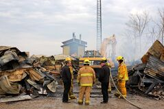 Members of Decker Hutterite Colony chat with area firefighters as the remains of their large mechanic shop smoulder on Monday morning. Vehicles from the colony were stored in the shop, but many were retrieved before the fire consumed sections of the building. No one was injured in the blaze, which is believed to have been caused by a lightning strike.