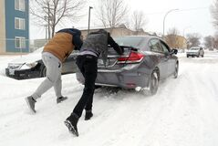 A pair of passersby help push a motorist from a snow-clogged section of 15th Street near Pacific Avenue during a fierce late-season snowstorm on Tuesday afternoon. The storm coated streets and roads with ice and dumped a large load of snow on top of that.