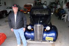 Bob Allen, in his garage with his classic vehicles, including his 1937 Chevrolet, right next to him.
