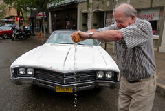 Dave McClelland wrings out rainwater from cleaning off his 1967 Buick during the monthly Cruise the Dub night along Rosser Avenue in downtown Brandon on June 5.