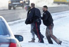 With guns drawn Brandon Police Service members march a suspect in a string of car robberies up to a police car after a stolen Buick LeSabre hit the ditch on Highway 110 east of Brandon after a police pursuit on Tuesday morning. Two suspects, a man and a woman, were taken into custody.