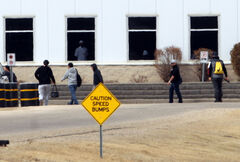 Workers enter the Maple Leaf Foods plant on Monday afternoon.