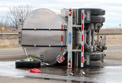 A fuel tanker lies on its side spilling thousands of litres of fuel after a collision between two semi-trucks at the intersection of Richmond Avenue East and Highway 110 east of Brandon on Monday.