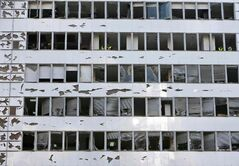 Workers clean shattered glass from broken windows at a damaged business center at the scene of an explosion, in central Beirut, Lebanon, Friday, Dec. 27, 2013.