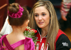 Lawrence receives a bouquet of roses from a young figure skater.