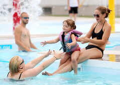 Sienna Seafoot, 3, slides down the legs of her mother Marisa Cline to be caught by Amanda Navid while swimming at the Wawanesa and District Water Park on Monday.