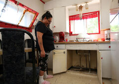 Fiona St. Paul looks under her sink at her home last month. She says even though she's having problems finding a place to live in Brandon, she'd rather live in the city than on a reserve because it doesn't offer her children opportunity and hope.